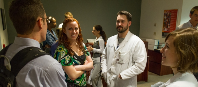 men and women in white lab coats conversing