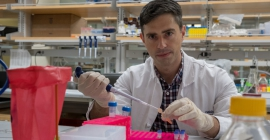 man in lab coat using pipet