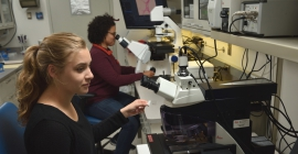 Two students looking in microscope