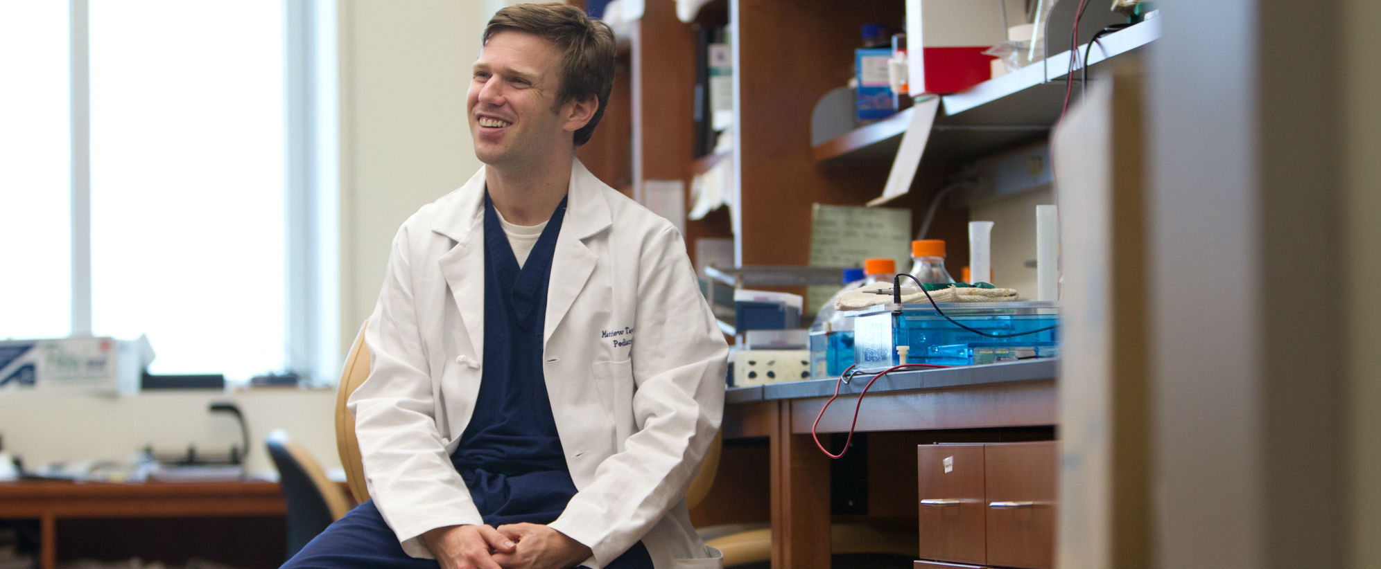 man in white coat sitting in lab